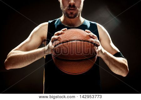 The silhouette view of a basketball player holding basket ball on black background. The hands and ball close up