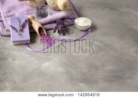 Spa composition with lavender, towel and salt on gray background