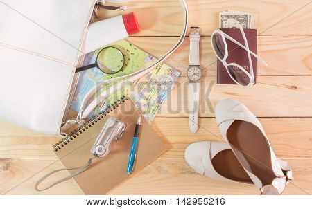 Travel concept with leather handbag sunglasses digital camera world map passport money note pad pen magnifying glass compass female shoes body lotion and wristwatch on wooden table