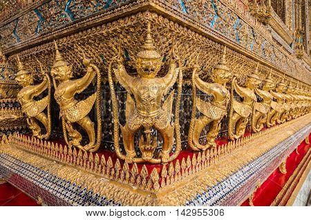 BANGKOK THAILAND - MARCH 28 2016: The ancient wood craft of Garudas and Nagas at the outside of the ubosot the main building of Wat Phra Kaew in Bangkok Thailand.