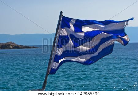 Greek flag on a sailing ship with greek coast near mountain Athos in background, Greece