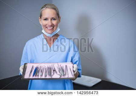 Portrait of smiling dental assistant holding tray with equipment in dental clinic