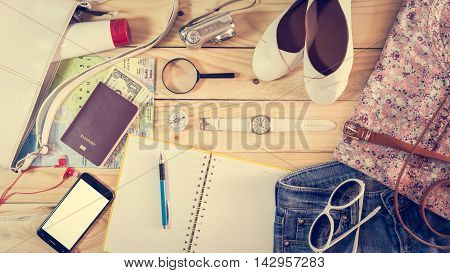Travel concept with set of female costumes and accessory on wooden vintage table