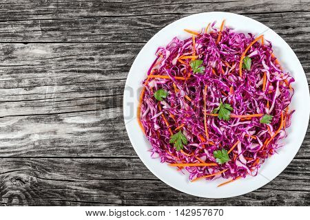 Salad coleslaw - red cabbage with carrots on white dish on old rustic boards side dish authentic classic recipe view from above blank space for text left