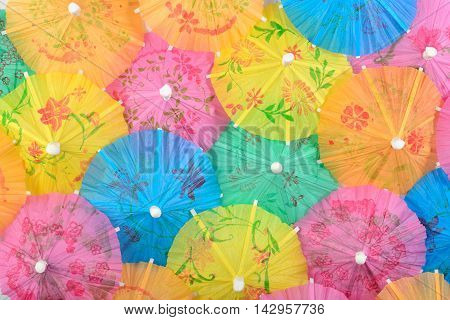 Colorful paper cocktail umbrella close-up as background