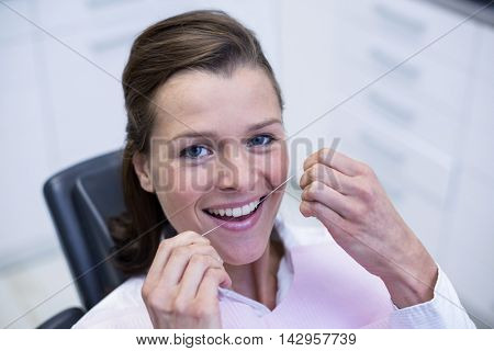Female patient flossing her teeth in dental clinic