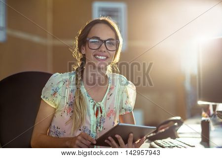 Portrait of smiling business executive using digital tablet in office