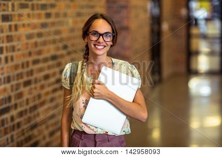 Portrait of business executive holding a laptop in office