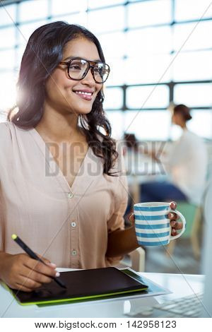Businesswoman using graphic tablet in office