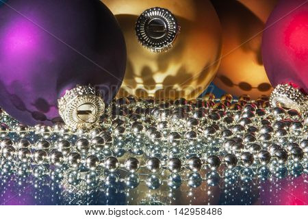 Colorful christmas balls and bead chain with reflections