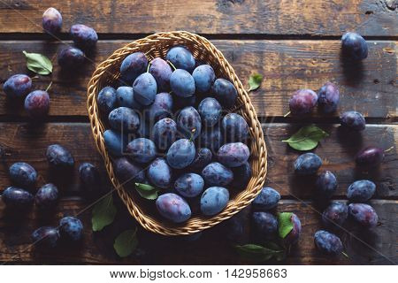 Freshly picked organic plums on a wooden table