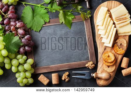 Red and white grapes, cheese board and chalkboard for your text. Top view with copy space