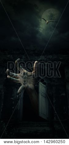 Zombie hand rising out from old ancient window with bird fly over dark sky and moon Halloween concept