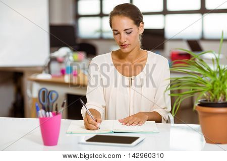 Business executive writing in diary in office