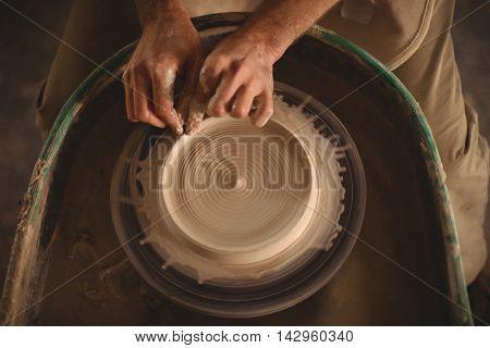 Hands of potter making a pot in pottery workshop