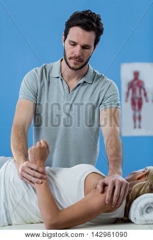 Male physiotherapist giving arm massage to female patient in clinic
