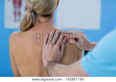 Male physiotherapist giving shoulder massage to female patient in clinic