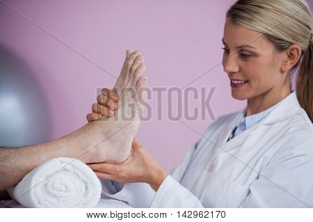 Physiotherapist giving foot massage to a patient in clinic