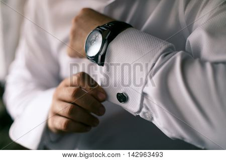 man in white shirt buttons on the hand cuffs to the clock