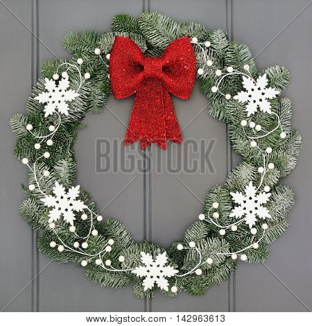 Christmas wreath with white snowflake and red bow decorations with snow covered blue spruce fir on grey front door background.