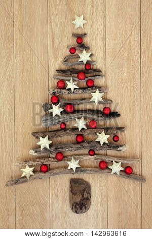 Driftwood christmas tree with star and red bauble decorations over oak wood background.