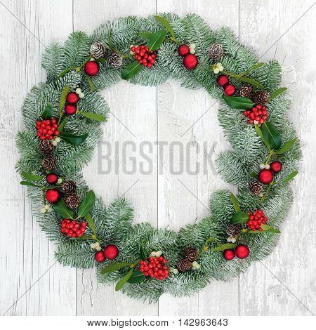 Christmas wreath decoration with red bauble decorations, holly, snow covered blue spruce fir and mistletoe over distressed white wood front door background.