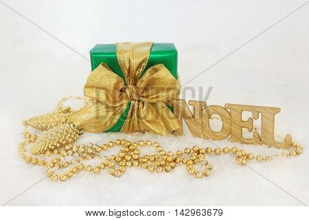 Christmas gift box with gold bow, glitter noel sign, pine cone baubles and bead decorations on snow background.