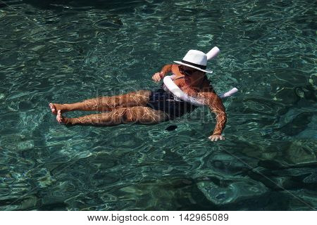 A lady relaxing in the clear sea waters while on vacation, 2016