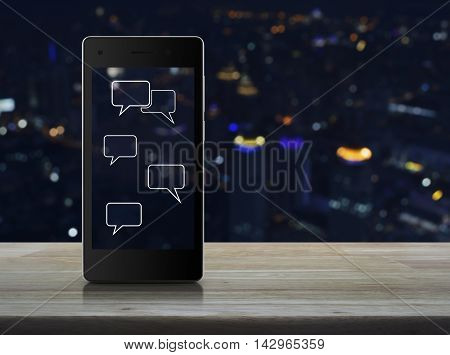 Social chat sign and speech bubbles on modern smart phone screen on wooden table over blur light city tower Social network concept
