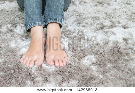 Closeup foot of asian woman sitting on gray carpet floor textured background in house