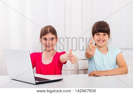 Cute little girls are using laptop and showing thumbs up.
