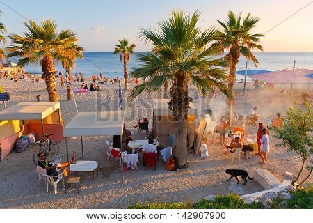 ATHENS, GREECE - AUGUST 13, 2016: People having a barbecue on the beach in Palaio Faliro neighborhood in Athens on August 13, 2016.