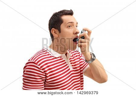 Young man using an asthma inhaler isolated on white background