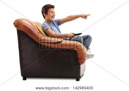Excited kid seated on an armchair watching something funny on tv isolated on white background