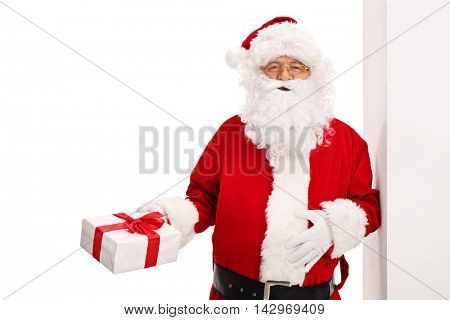 Santa Claus leaning against a wall and holding a present isolated on white background