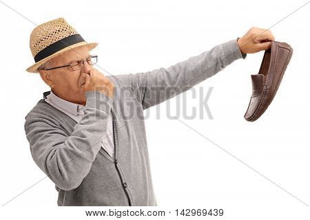 Disgusted old man holding a smelly shoe isolated on white background