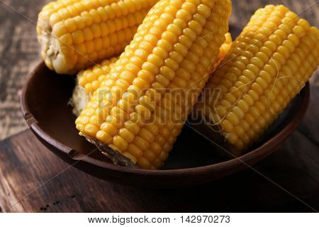 close view on Homemade golden corn cob with butter and salt on table.