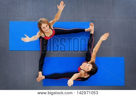 Sport instructors team in sportswear. Top view of two happy young women with slim body stretching on mat during pilates fitness classes. Sporty people healthy lifestyle and group physical exercises.