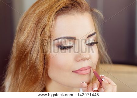 Woman is doing professional makeup. Bride doing makeup in the morning in a room. Wedding makeup. Makeup artist doing makeup for beautiful girl. Morning of the bride