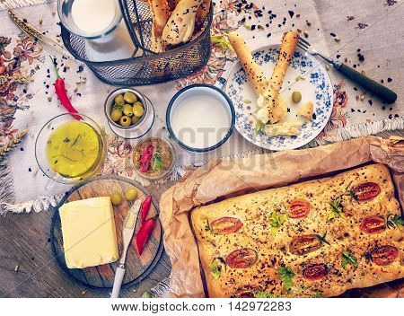 Traditional Focaccia With Tomatoes And Bread Sticks.