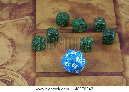 One clear blue dice with seven green dices on the orange background