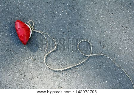 red purse with a rope tied to it is on the road view from above / caution dangerous bait