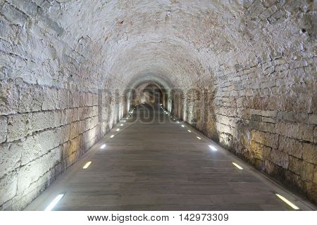 Old rock Tunnel at The Panathenaic Stadium with lights on both sides of the floor and a curve at the end. It is located in Athens, Greece, and it was built in the 6th century BC. The purpose of this Tunnel was that the athletes came down by it to get to t