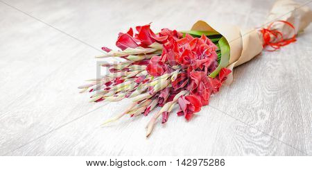 Red gladiolus bouquet wrapped in paper on a light wooden background. Images for backgrounds and printed materials.