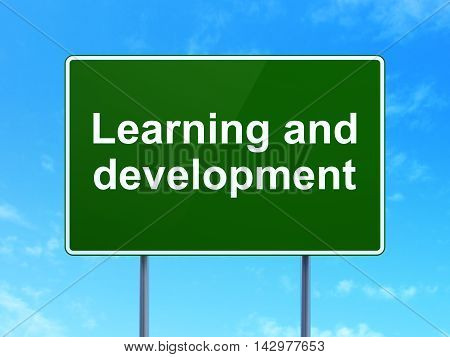 Studying concept: Learning And Development on green road highway sign, clear blue sky background, 3D rendering