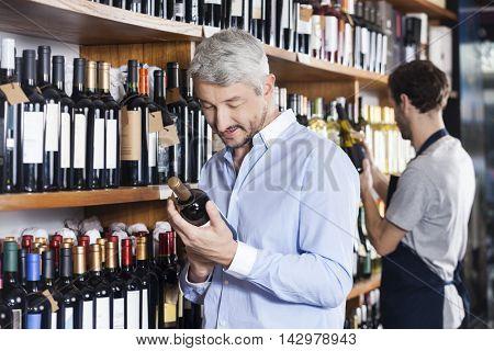 Customer And Salesman Looking At Wine Bottles