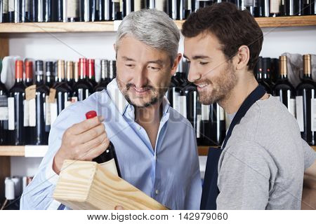 Customer And Salesman Looking At Wine Bottle
