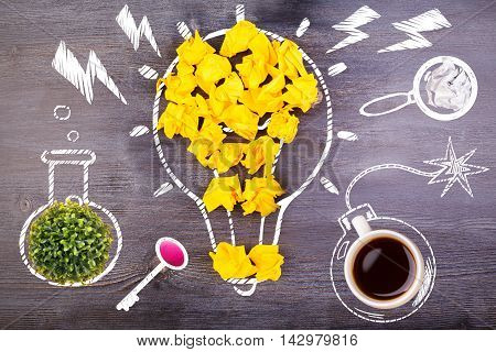 Top view of dark wooden desktop with creative and abstract crumpled paper lightbulb coffee cup bomb plant test-tube eraser key and magnifier. Idea concept