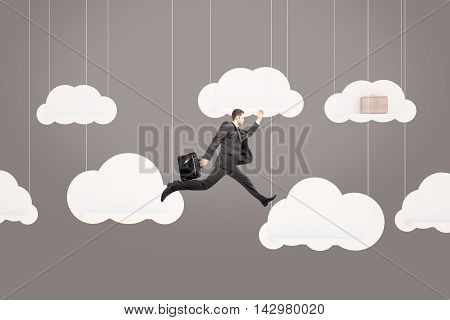 Running businessman chasing suitcase on abstract clouds. Grey background. Success concept