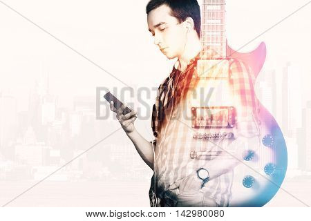 Casual guy listening to music and an electric guital on light background with city view and copyspace. Double exposure